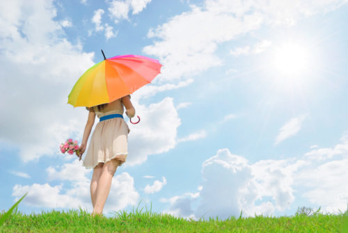 青空の下虹色パラソルをさす女性