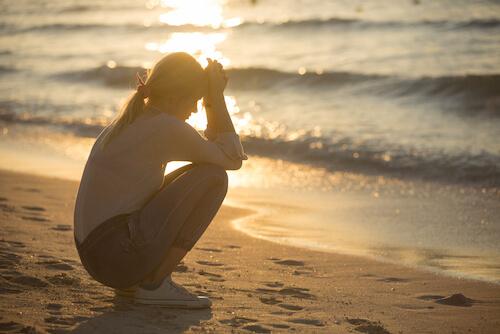 海辺で落ち込む女性