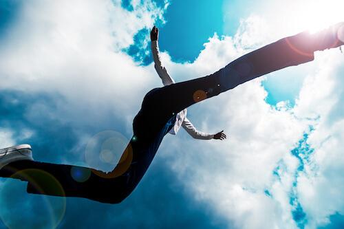 青空の下ジャンプする男性