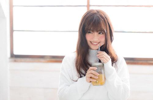 ドリンクを飲む笑顔の女性
