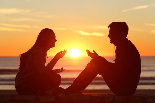 夕日の中楽しげに話す男女